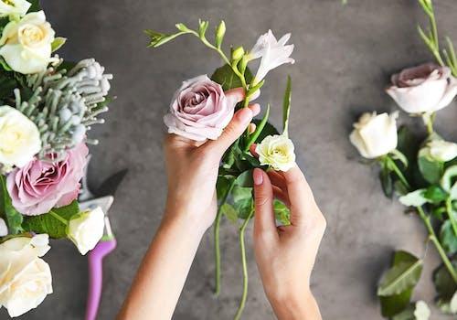 The skilled hands of a floral designer, carefully arranging a bouquet