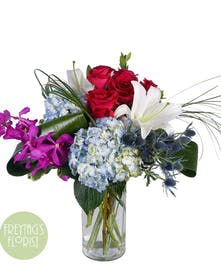 cylinder vase with hot pink roses, blue hydrangea, white lilies, purple orchids and blue thistle.