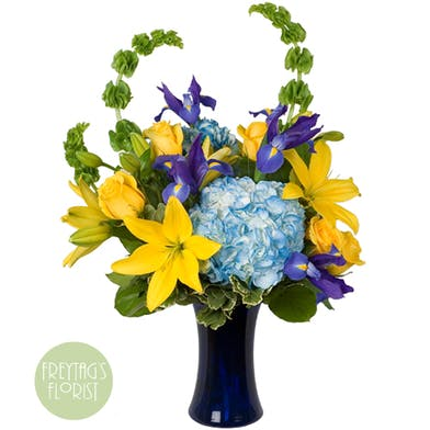 Blue flowers and yellow flowers in a blue vase