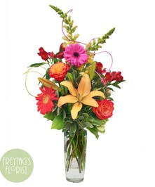 Yellow and orange flowers with greenery in a clear glass vase.