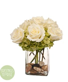 White roses and green hydrangea in a rectangle vase.