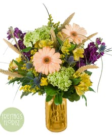 Summer garden and wildflower bouquet arranged in an amber 'sweet tea' mason jar style vase.