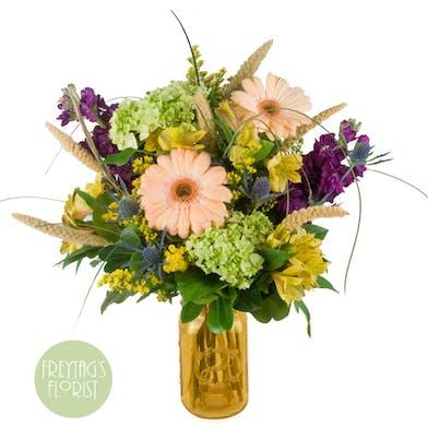 Summer garden and wildflower bouquet arranged in an amber 'sweet tea' mason jar style vase.